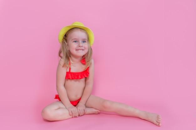 赤い水着と帽子にピンクの背景に座っている笑顔の美しいブロンド少女。夏の家族休暇のコンセプトは、海で休む。