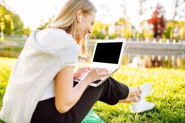 公園の芝生の上に座っているコンピューターで働く女の子やビデオチャット