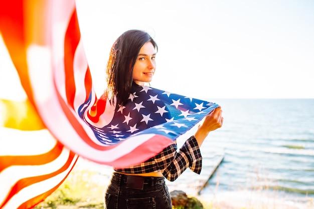 Молодая патриотическая женщина держит американский флаг на ветру на пляже на закате