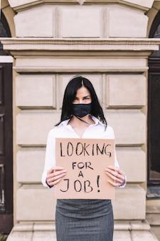 黒い顔のマスクを着ている仕事を探して看板を持っている若いビジネス女性。コロナウイルス後の失業。