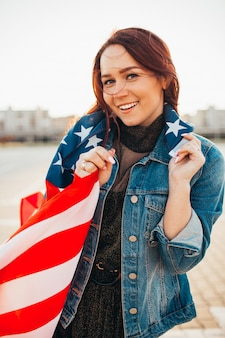 日差しの中でアメリカの国旗に包まれた若いかなり赤い髪の女性。