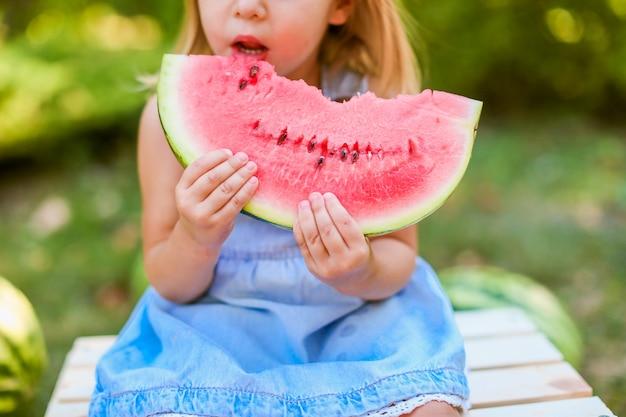 庭でスイカを食べる子供。子供たちは屋外で果物を食べる。子供のための健康的なスナック。