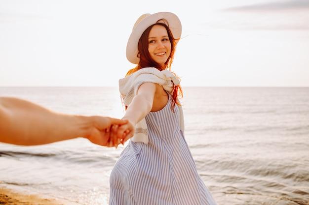 Улыбается длинноволосая женщина в шляпе, держа руку парня вдоль пустой океан пляж песок на закате