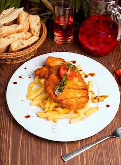 Жареная куриная грудка с картофелем фри в белой тарелке. быстрое питание