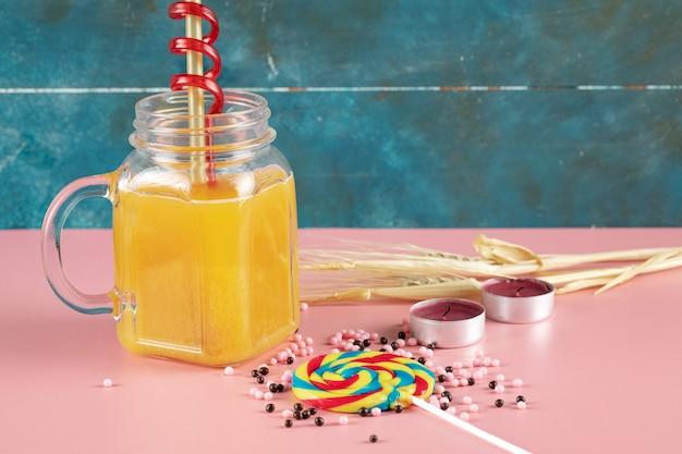 周りのアイスキャンデーのガラスの瓶にオレンジジュース