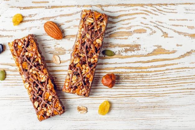 Здоровые батончики с шоколадом, батончики мюсли с орехами и сухофруктами, вид сверху