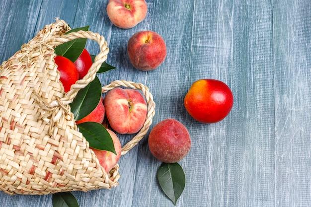 枝編み細工品バスケットから取り出した桃、ネクタリン、桃のイチジク