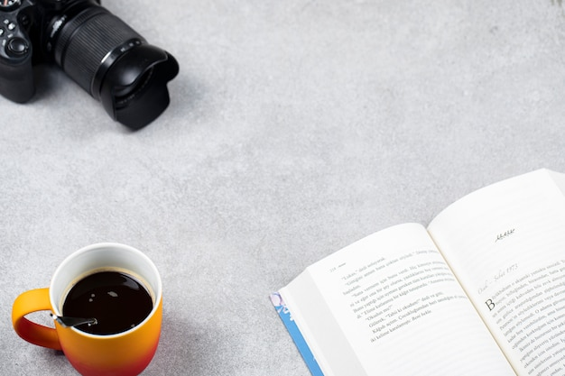 Чашка эспрессо с книгой и фотоаппаратом на столе