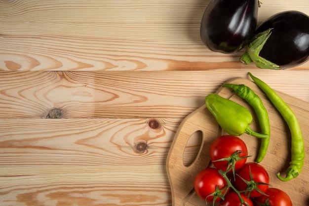 緑の唐辛子とトマトの木製のテーブル