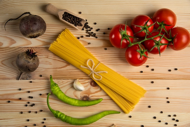 唐辛子とスパゲッティの周りのトマトの束