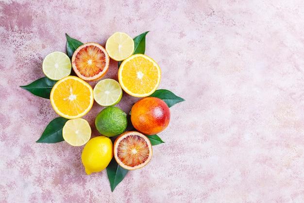 Цитрусовый фон с ассорти из свежих цитрусовых фруктов, лимон, апельсин