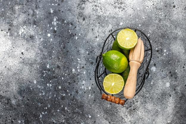 Свежий лайм с деревянной цитрусовой соковыжималкой, вид сверху