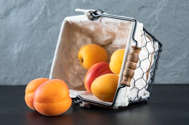 Свежие абрикосы в белой металлической корзине