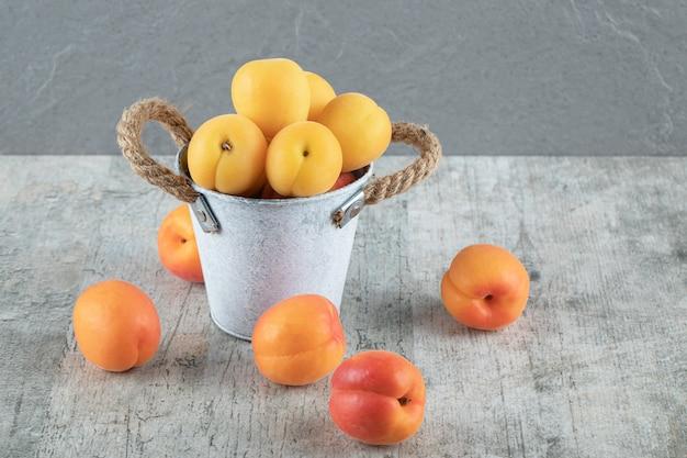 Персик и абрикосы в серебряном контейнере