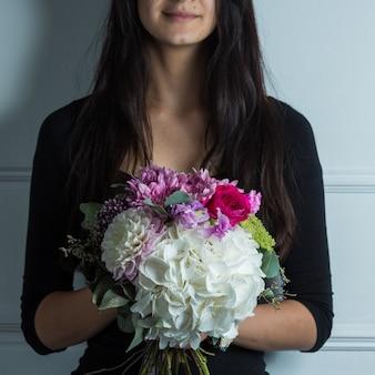 混合季節の花の花束を保持し、促進する女性