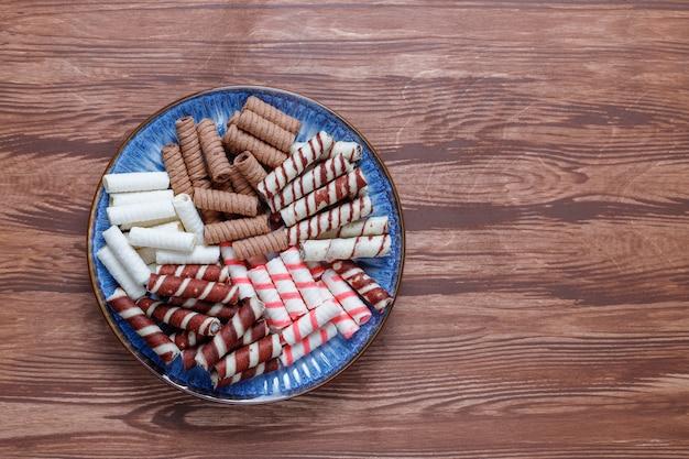 Различные вафельные трубочки в керамические тарелки, вид сверху.