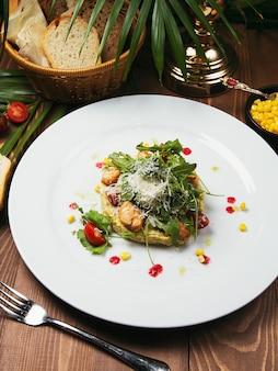 新鮮な野菜とチキンのシーザーサラダ。木のテーブル、おいしいサラダの白いプレートのサラダ