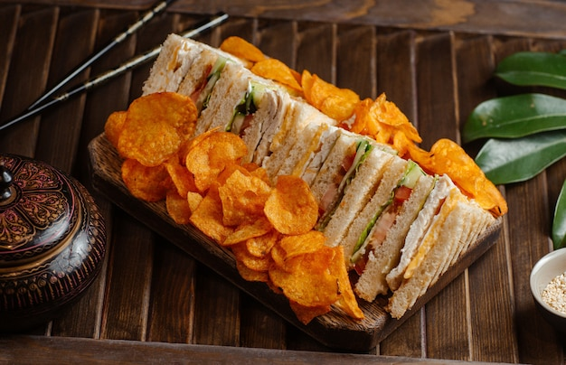 狭いプレートにチップを入れたクラブサンドイッチ