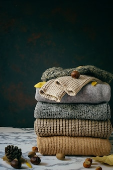 居心地の良いニットセーターのスタック。秋冬コンセプト、ニットウールセーター。ニットの冬服、セーター、ニットの山