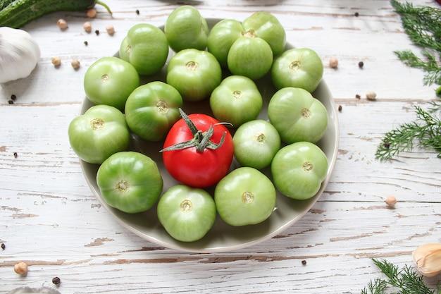 Зеленые помидоры, соленые огурцы на белом деревянном столе с зеленым и красным и чили перцем, фенхелем, солью, черным перцем, чесноком, горохом, крупным планом, здоровая концепция, вид сверху, плоская планировка