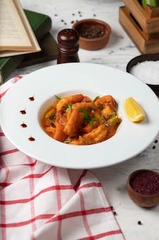 Куриные ножки тушеные в томатном соусе в белой миске с овощами и лимоном.