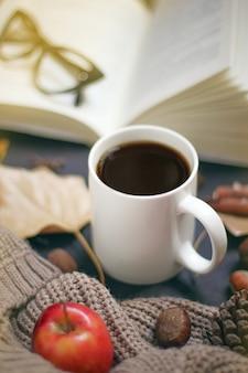 Осень, осенние листья, горячая дымящаяся чашка кофе и теплый шарф или кардиган. сезонный, утренний кофе, воскресенье расслабляющий и натюрморт концепции.