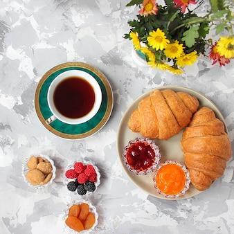 フランスの朝食、クロワッサン、アプリコットジャム、チェリージャム、紅茶、赤と黄色の花