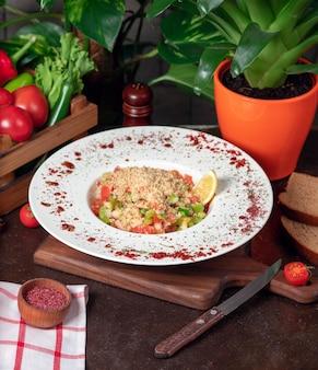 野菜、トマト、きゅうりのクラッカーサラダ。スマークとレモンの白い皿の中の台所のテーブルの上のサラダ