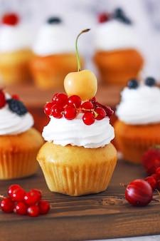 Сладкие ванильные кексы с начинкой из ягодного джема и сырным кремом, украшенные летними ягодами