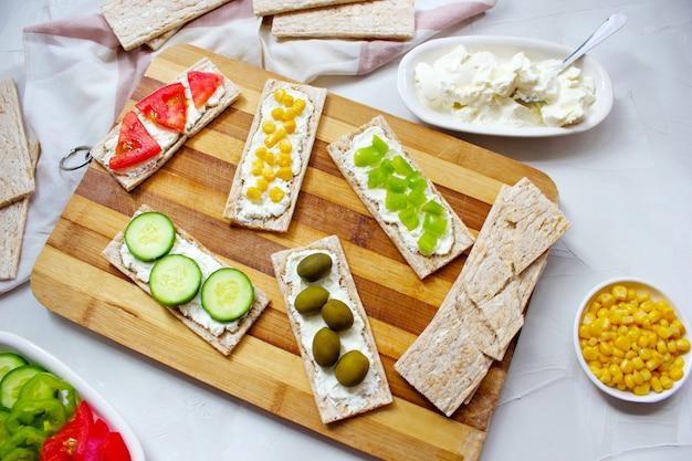 カッテージチーズとグリーンオリーブ、キャベツ、トマト、コーン、まな板の上のピーマンのスライスと自家製クリスプブレッドトースト。健康食品のコンセプト、トップビュー。フラットレイ