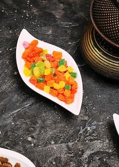 黒いテーブルの上の皿に甘い色のゼリージューシーマーマレードがたくさん