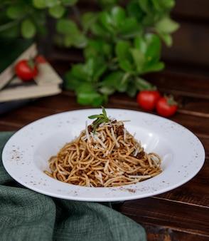Итальянские спагетти с листьями мяты сверху на тарелке