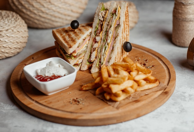 サクサクしたフライドポテト、スナック、スティック、木の板にケトカップ付きのクラブサンドイッチ