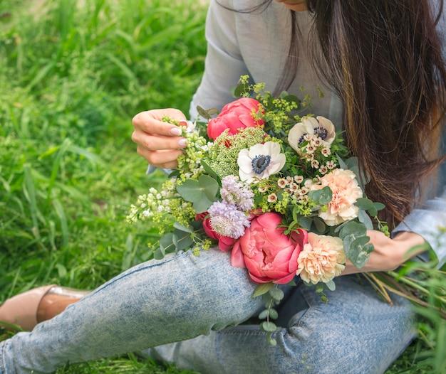 手に色とりどりの花の花束を保持し、緑の草の上に座っている女性
