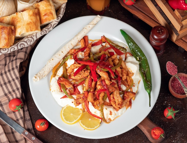 Фахита из курицы, куриное филе, обжаренное с болгарским перцем в лаваше с кусочками хлеба в белой тарелке