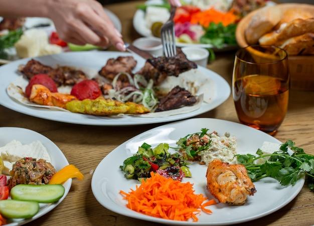 Обед в белых тарелках с мясом и овощами, закусками, продуктами.