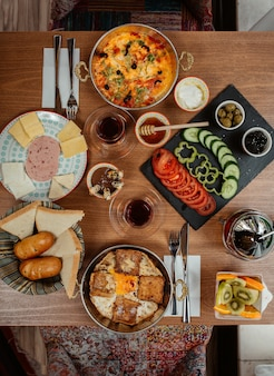 Обильный стол для завтрака с широким выбором блюд, включая яйца, колбасы, сливочный сыр