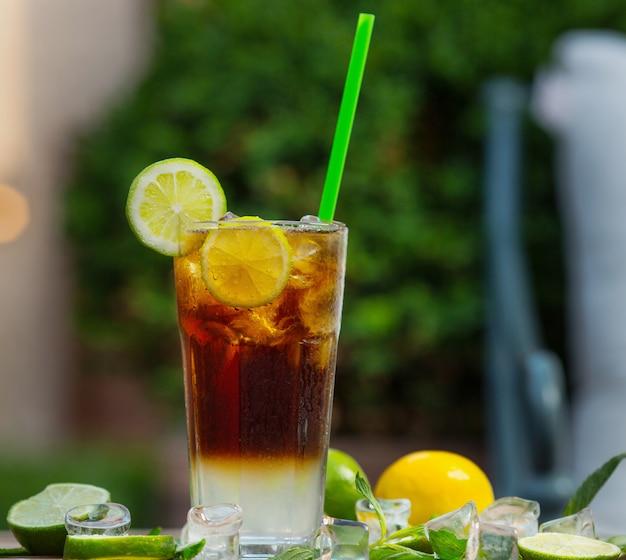 レモンのスライスと赤いカクテルモヒートのガラス、レストランの背景にライム-画像