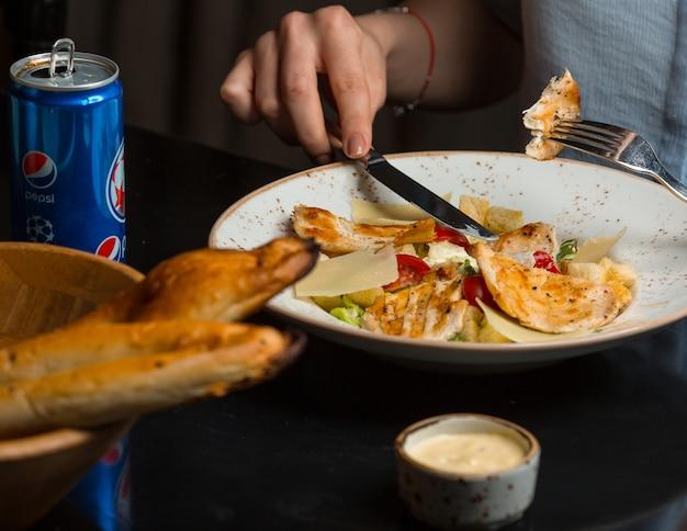 チキンのグリルとチェリートマトのパスタを食べる女性