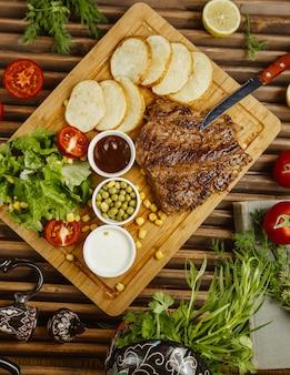木製テーブルの上に丸いローストポテトを添えたビーフステーキ、グリーンサラダ、豆、マヨネーズ添え
