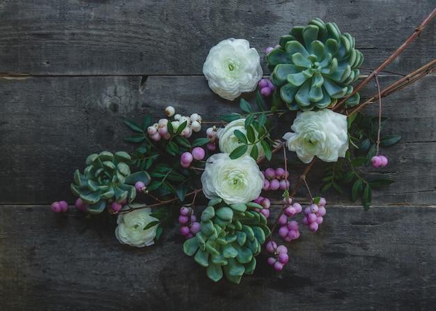 木製のテーブルに白と紫の花の花の枝。