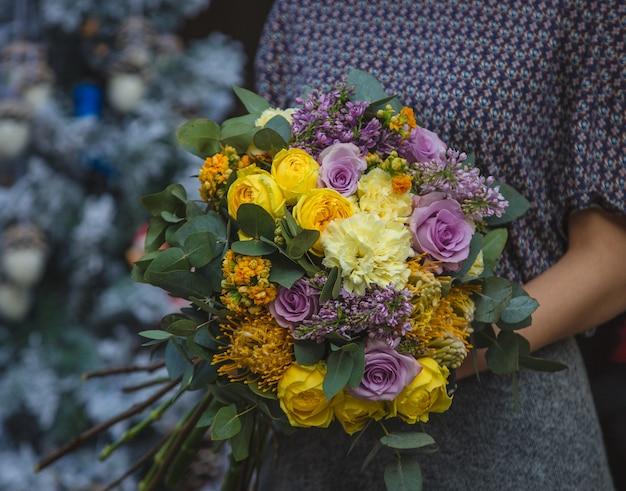 秋の秋の色の花の花束を手に持った女性