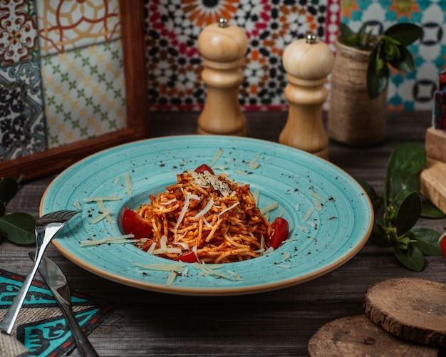 ブルーの本格的なボウルの中にトマトソースのイタリアンパスタ