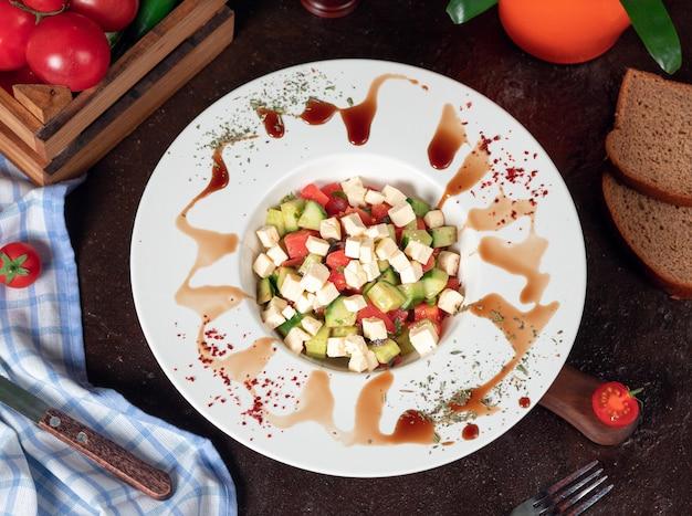 野菜、トマト、きゅうり、ロカサラダ。スマークとレモンの白い皿の中の台所のテーブルの上のサラダ