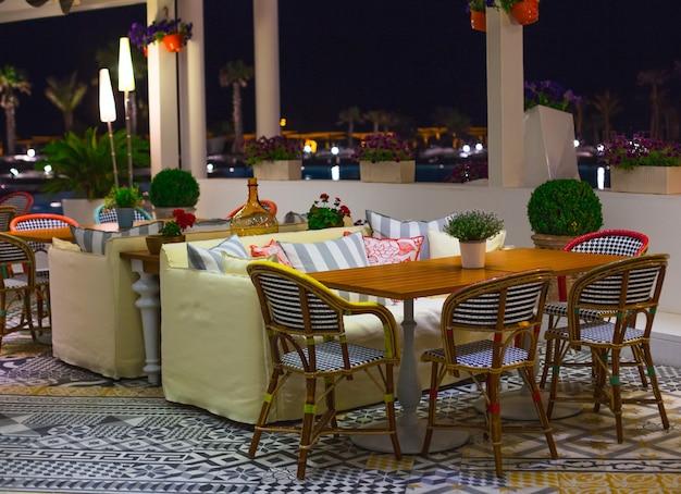 パノラマの景色を望むレストランの椅子と黄色いソファのあるテーブル。