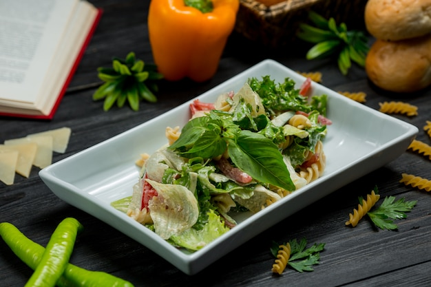 Зеленый салат с листьями свежей мяты и нарезанным пармезаном в квадратной тарелке.