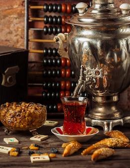 Традиционный самоварный чайный сервиз с разнообразными закусками, сладостями и сухофруктами.