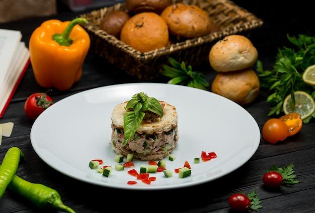 Ризотто с грибами внутри белой тарелки со свежими листьями мяты на вершине