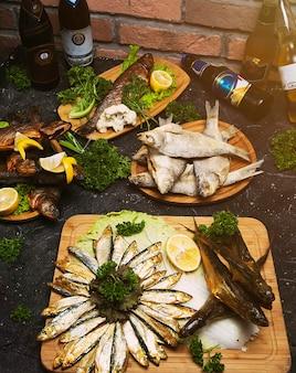 Рыбное блюдо, приготовленное из различных ингредиентов и видов рыбы. сырой морской окунь с лимоном, чесноком, зеленью и специями на разделочной доске. концепция здорового питания или диетического питания.