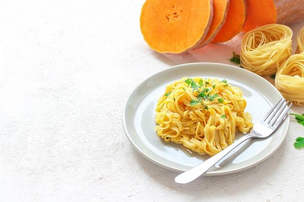 新鮮な生のバターナットスカッシュスライスのセラミックプレートのカボチャアルフレドフェットチーネパスタ。秋の昼食。バターナットスカッシュのレシピ。